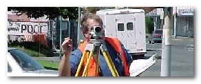 Man with a safety vest on looking through a camera